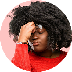 Black woman touching her forehead as if in pain